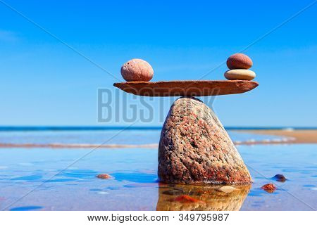 Symbolic Scales Made Of Stones On The Sea Background. Concept Of Harmony And Balance. Pros And Cons,