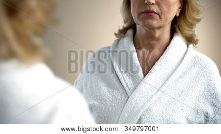 Displeased Elderly Woman Looking At Her Neck In Front Of Mirror, Aging Process