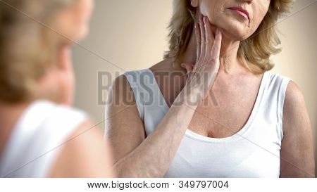 Aged Woman Looking In Mirror At Wrinkled Skin, Thinking About Plastic Surgery