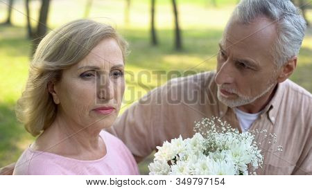 Apologizing Man Giving Flowers To Woman, Crisis In Relations, Couple Quarrel