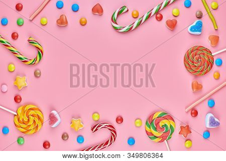 Sweet Candy Copy Space Frame With Lollipops On Pink Background. Love To Colorful Sweetmeats In Child