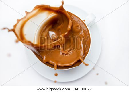 Overflowing cup of white coffee against white background