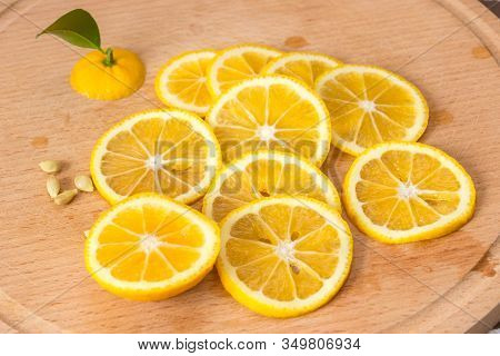 Sliced Orange-yellow Lemon Of Volkamer With A Small Green Leaf And Seeds On A Wooden Board, Indoor C