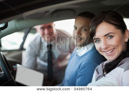 Smiling couple in a new car with a salesman