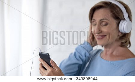 Retiree Lady In Headphones Listening To Music On Mobile Phone And Smiling