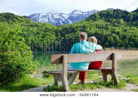 Mature couple enjoying view of lake and mountains