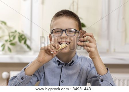 Smiling Boy With Glasses Sits At The Table And Holds Sweets In His Hands. In One Hand He Holds White