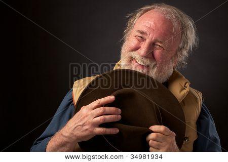 Friendly smiling senior man holding his hat