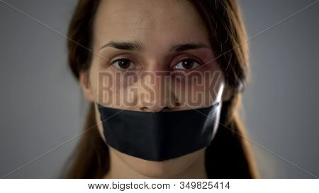 Bruised Woman With Taped Mouth Looking At Camera, Terrorist Hostage, Fear