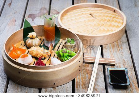 Several Different Traditional Chinese Dimsum Dumplings In A Wooden Basket Cooked For Guests On A Woo