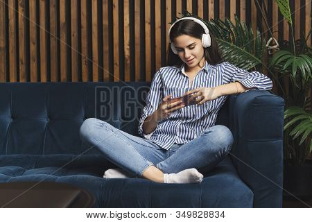 Girl Wearing Headphones Texting On Smartphone To Friend Online. Young Woman Streaming Music On Mobil
