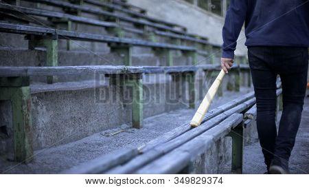 Young Man Walking On Stadium Tribune With Baseball Bat, Youth Gang, Vandalism