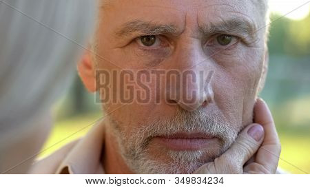 Sad Retired Man Looking Into Camera, Woman Supporting Husband, Close-up View