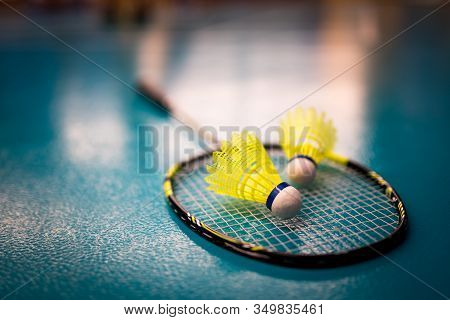 Badminton Yellow Shuttlecock And Racket On Green Floor