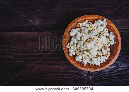 Popcorn In Wood Dish Or Bowl On Dark Wood Table