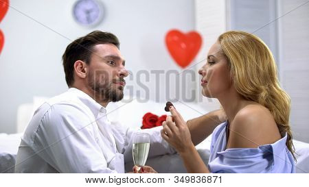 Couple Having Foreplay, Eating Chocolate And Drinking Champagne, Enjoying Time