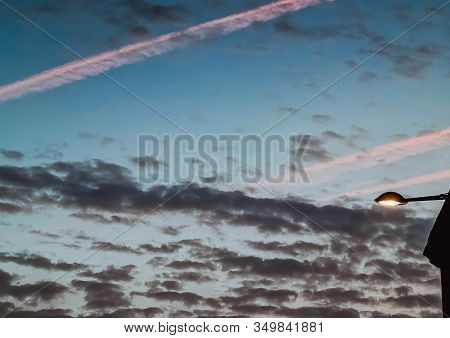 View Of House Next To A Street Light Against Dark Sky With Clouds, Airplane Traces, Jet Trail