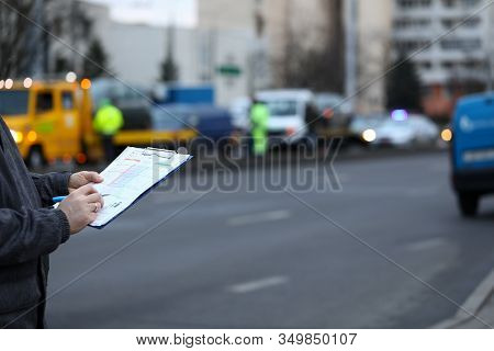 Filling Out Accident Statement At Scene Accident. Man Fills Document Standing On Road. Driver Draws