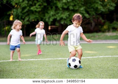 Football Game: Team Of Toddlers Playing Soccer On Green Field: Three Children, Two Boys (one Is Bare