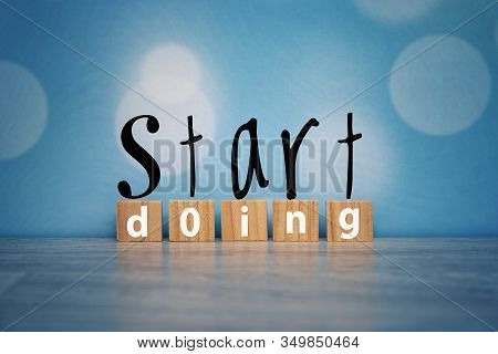 Motivational Words - Start Doing. With Single Word On Rustic Wooden Blocks On Vintage Soft Blue Boke