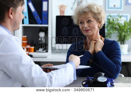 Signing By Patient Medical Intervention Document. Doctor Gives Elderly Woman Medical Document For Si