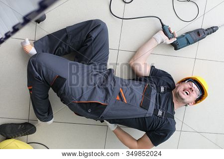 Severe Pain In Back Builder, Man Lies On Floor. Man In Work Clothes And Helmet Lies On Floor With Wr