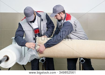 Men Workers Packing Carpet In A Plastic Bag After Cleaning It In Automatic Washing Machine And Dryer