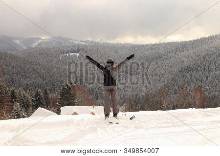 Young Girl Takes A Deep Breath And Exhales Air From The Mountains. Professional Female Skier Enjoy A