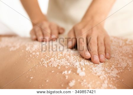 Young Woman Having Body Scrubbing Procedure With Sea Salt In Spa Salon, Closeup