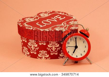 A Red Heart Shaped Gift Box And An Alarm Clock Over A Pink Background Remind A Romantic Couple Of Im