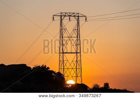 Sunrising below hilltop electric power tower at Santa Susana Pass State Historic Park in Los Angeles California.