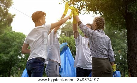 Team Of Volunteers Hi-fiving During Collecting Garbage In Park, Save Nature