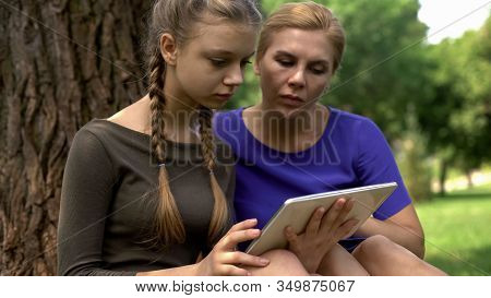 Mom And Daughter Reviewing College Programs On Tablet To Apply, Online Services