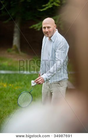 Portrait of mature man in casual wear with racquet and birdie ready to serve
