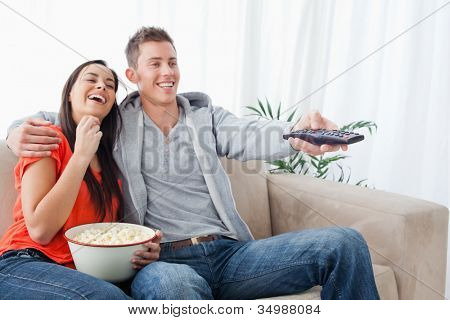 A laughing couple on the couch embracing with popcorn as they watch a tv show