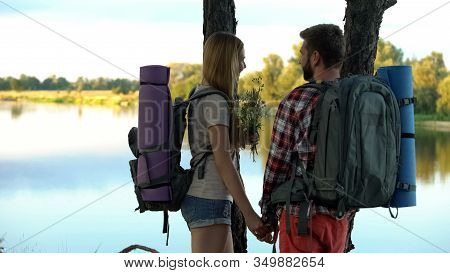 Boyfriend With Lady Watching River Scape, Holding Field Flowers, Green Tourism