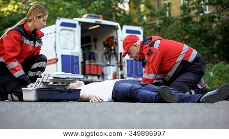 Ambulance Crew Helping Unconscious Man On Road, First Aid At Car Accident Scene
