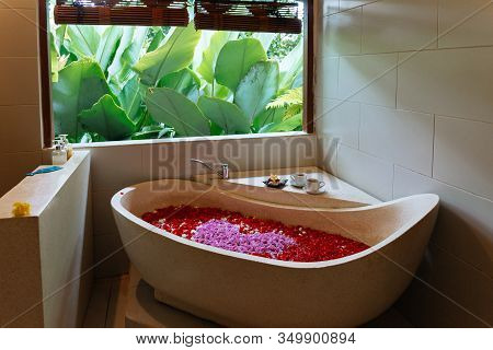 Stone Bath Tub With Heart Shaped Flower Petals Near Window With Jungle View. Organic Spa Relaxation