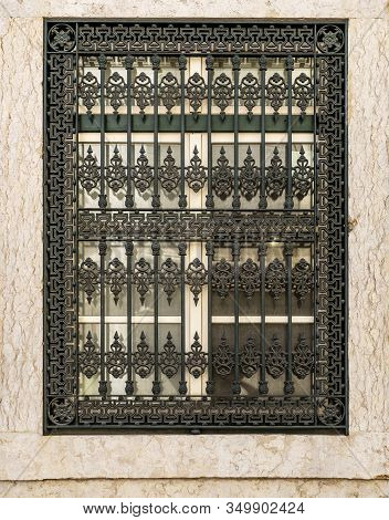 Detail Of An Elaborated Vintage Iron Grill Covering A Window On An Old Building In The Historic Cent