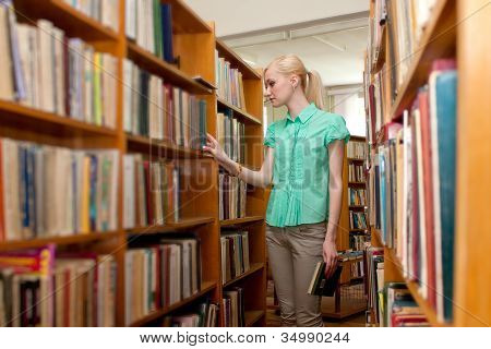 Young girl in the library looking for a book