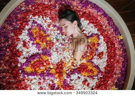 Close Up Portrait Of Woman Relaxing In Round Big Bath With Tropical Flowers. Amazing Huge Bath Tub I