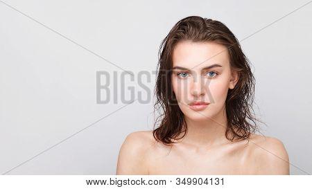 A Young Girl With Long Wet Loose Hair With Bare Shoulders Looks At The Camera. Close Up Portrait On