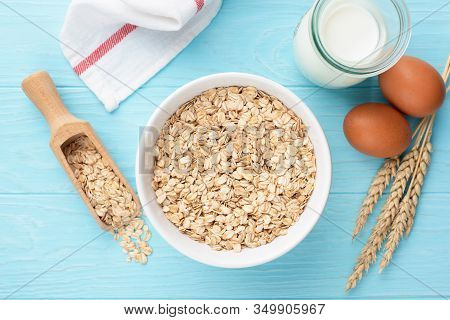 Oat Flakes Or Rolled Oats In Bowl, Bottle Of Milk And Chicken Eggs. Blue Wooden Table Background. Ta