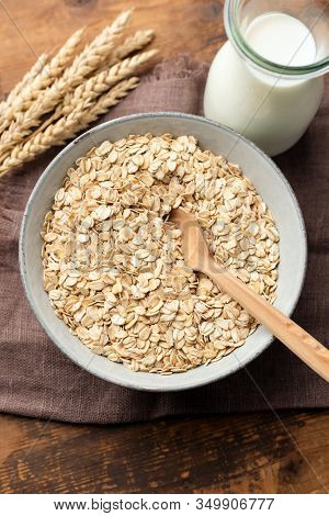 Oat Flakes, Rolled Oats In Bowl On A Wooden Table Background. Healthy Eating, Dieting Concept