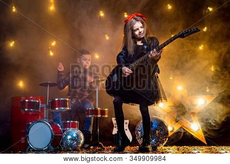 Kids Pretending To Be In A Rock Band And Play And Sing At Studio Or Stage. Girl Play On Guitar And B