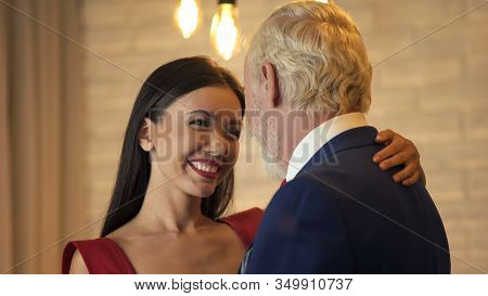 Young Woman Flirting And Dancing With Old Millionaire On Date, Escort Service