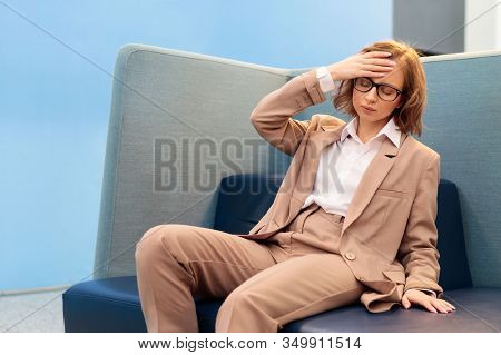 Exhausted Female Worker Having Strong Tension Headache Or Head Migraine, Feeling Pressure, Holding H
