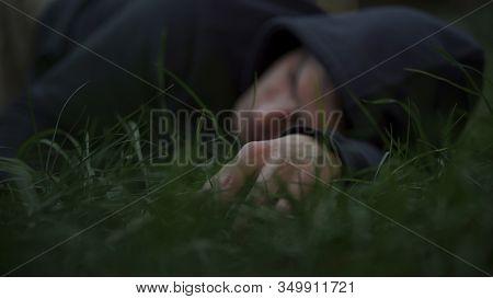 Victim Of Thugs Lying On Grass, Mans Corpse, Murdered Citizen, Crime Scene