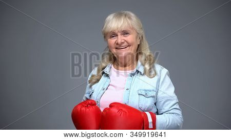 Happy Retiree Woman In Boxing Gloves On Gray Background, Self-belief Concept
