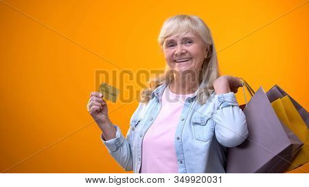 Joyful Retiree Lady Showing Shopping Bags And Golden Card, Standing Customer